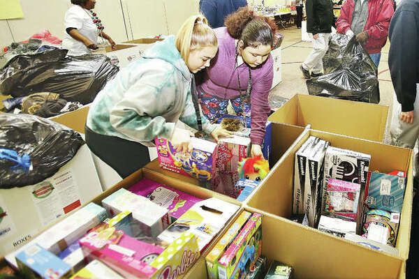 Alton High School juniors Aaliyah Jones, left, and Sandy Graves, right, sort donated items to the United Way's Community Christmas Thursday in the Main Street United Methodist Church in Alton. The items will be delivered today to 16 United Way organizations.