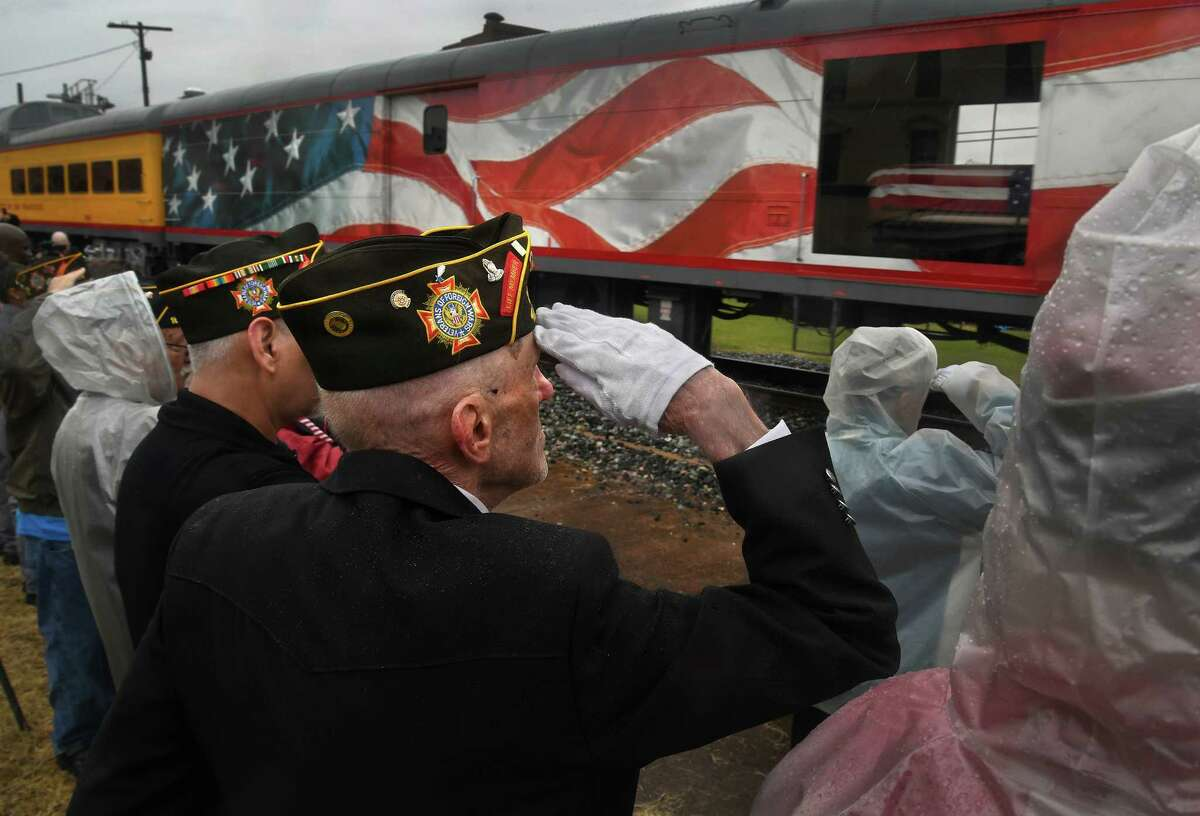 Retired Air Force Staff Sgt. Carl Dry salutes Thursday as the flag-draped casket of former president George H.W. Bush travels by train through Navasota, Texas, on its way to College Station for burial.