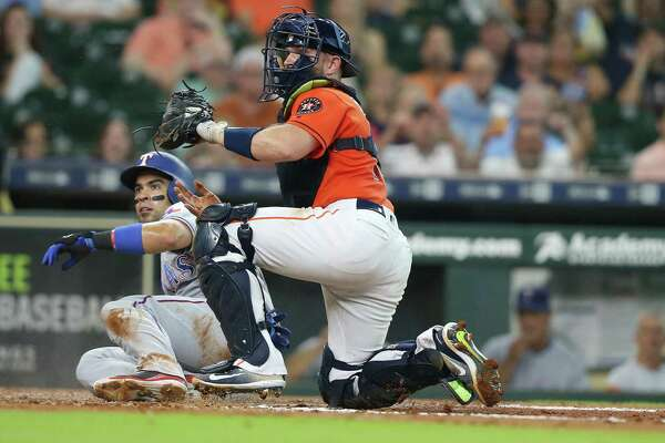 Texas Rangers catcher Robinson Chirinos (61) slides safely at home under Houston Astros catcher Max Stassi (12) after a sacrifice bunt by Texas Rangers center fielder Carlos Tocci (15) in the second inning at Minute Maid Park on Friday, July 27, 2018 in Houston.
