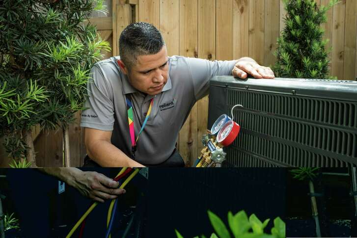 Reliant Energy heating, air conditioning and ventilation technician Argelio Garcia is checking an outdoor condensing unit ina customer's home.
