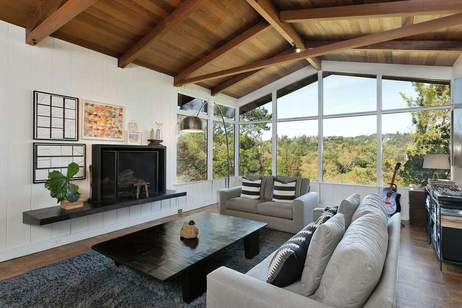The living room at 5 La Noria in Orinda has a raised fireplace, oversize windows and a vaulted, beamed ceiling. Below left: The deck off the family room looks out on tree-studded hillsides. Photo: Grubb Co.