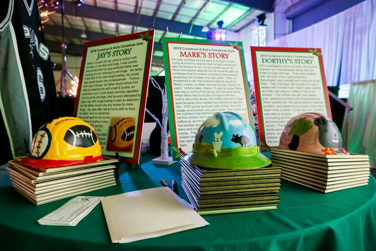 Three hardhats decorated by foster children wait to be auctioned off at the annual Construct a Kid's Christmas Gala at the Freeman Coliseum Expo Hall C on Thursday, Dec. 6 , 2018.