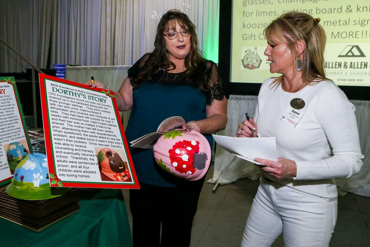 Sandee Morgan (left), vice president of Construct a Kid's Christmas, and Dawn Thompson with TACCA take the first of three hats decorated by foster children to be auctioned off at the annual Construct a Kid's Christmas Gala at the Freeman Coliseum Expo Hall C on Thursday, Dec. 6 , 2018. This first hat by Dorthy was sold to Perry Beyer of Beyer Plumbing for $5,000.