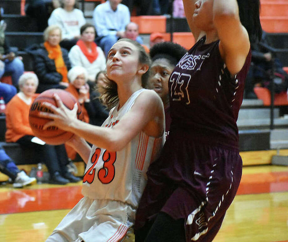 Edwardsville senior Megan Silvey, left, drives to the basket in the fourth quarter.