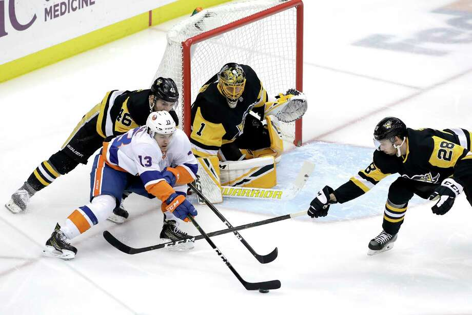 New York Islanders' Mathew Barzal (13) cannot get off a shot in front of Pittsburgh Penguins goaltender Casey DeSmith (1) with Penguins' Zach Aston-Reese (46) and Marcus Pettersson (28) defending during the first period of an NHL hockey game in Pittsburgh, Thursday, Dec. 6, 2018. (AP Photo/Gene J. Puskar) Photo: Gene J. Puskar / Copyright 2018 The Associated Press. All rights reserved