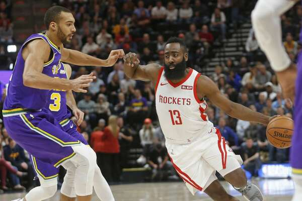 Houston Rockets guard James Harden (13) drives around Utah Jazz center Rudy Gobert, left, during the first half of an NBA basketball game Thursday Dec. 6, 2018, in Salt Lake City. (AP Photo/Rick Bowmer)