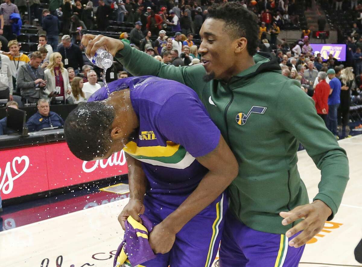 Utah Jazz guard Donovan Mitchell, right, pours water over the head of forward Derrick Favors, left, after the Jazz defeated the Houston Rockets 118-91 during an NBA basketball game Thursday Dec. 6, 2018, in Salt Lake City. (AP Photo/Rick Bowmer)