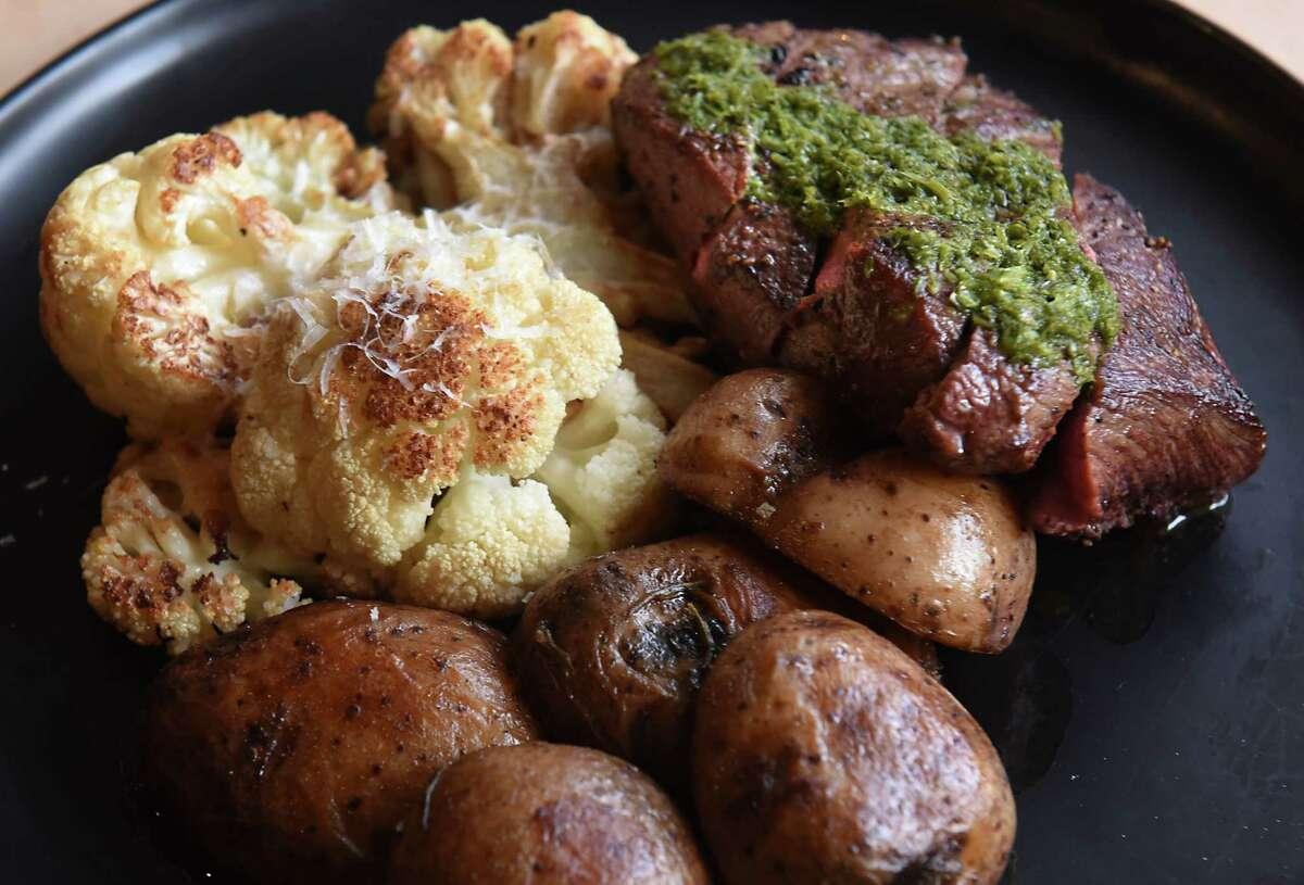 Chimichurrri steak -- sliced flat iron served with roasted potatoes and charred cauliflower -- is one of the few main plates at Dove + Deer. (Lori Van Buren/Times Union)