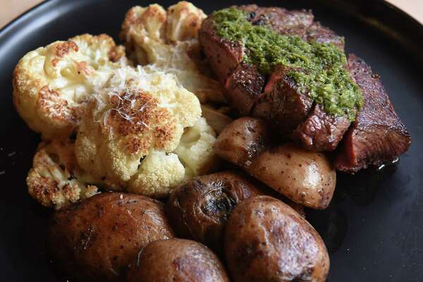 Chimichurrri steak -- sliced flat iron served with roasted potatoes and charred cauliflower -- is one of the few main plates at Dove + Deer. (Lori Van Buren/Times Union)