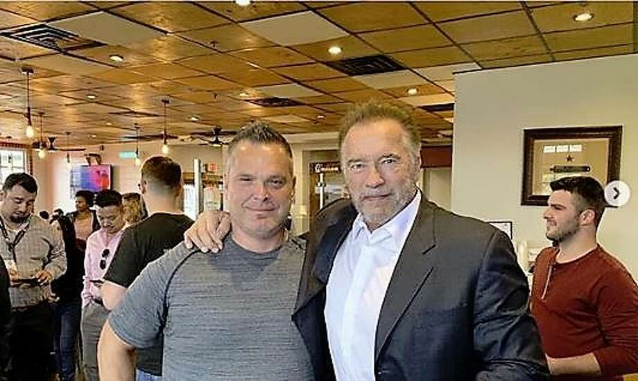 Schwarzenegger, right, and Ronnie Killen pose for a photo Thursday at Killen's Barbecue.