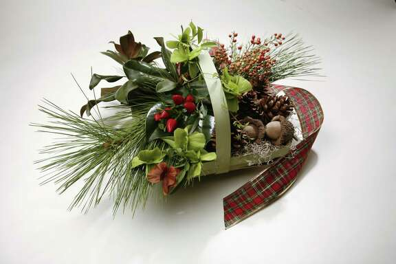 For holiday cheer, fill a garden trug with pine, magnolia, bur oak acorns, butterfly vine seed pods, nandina berries and red peppers.