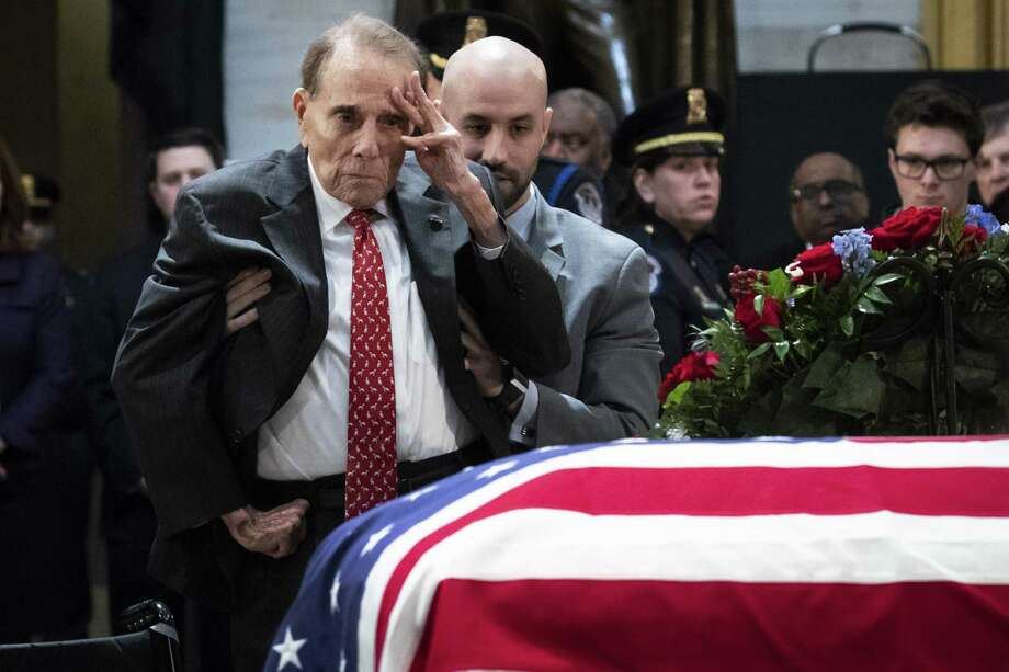 Former U.S. Sen. Bob Dole stands up and salutes the casket of the late former President George H.W. Bush as he lies in state at the U.S. Capitol, December 4, 2018 in Washington, D.C. Photo: Drew Angerer / Getty Images / 2018 Getty Images
