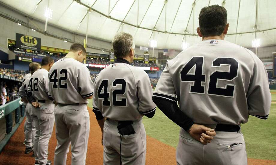Members of the New York Yankees, including Mark Teixeira, third from right, wear No. 42 in honor of Jackie Robinson during the National Anthem before an MLB game against the Tampa Bay Rays Wednesday April 15, 2009 in St. Petersburg, Fla. Photo: Chris O'Meara / AP / AP
