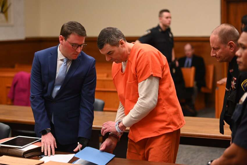 Michael Martin, right, a contractor who used two minority-owned businesses as fronts to fraudulently obtain public construction contracts worth $1 million and then failed to properly pay more than 50 employees speaks in Schenectady County court before the judge sentenced him to 12 years in prison.