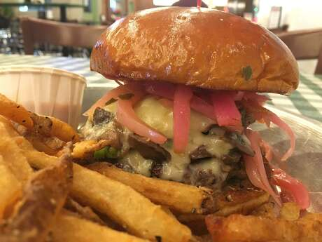 The 281-330-8004 burger at Rodeo Goat has roasted mushrooms, pickled onions and gruyere.