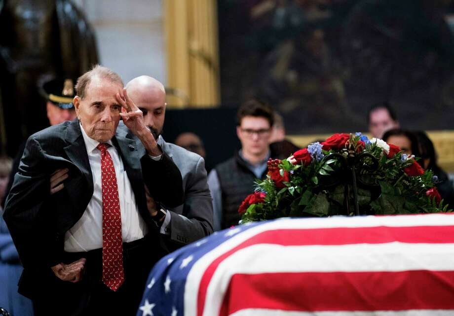 Former Sen. Bob Dole (R-Kansas) is helped to stand as he salutes the coffin bearing the remains of former President George H. W. Bush at the Capitol in Washington on Tuesday, Dec. 4, 2018. Bush will lie in state in the Capitol Rotunda with his coffin on display for public viewing until Wednesday morning. (Erin Schaff/The New York Times) Photo: ERIN SCHAFF, NYT / NYTNS