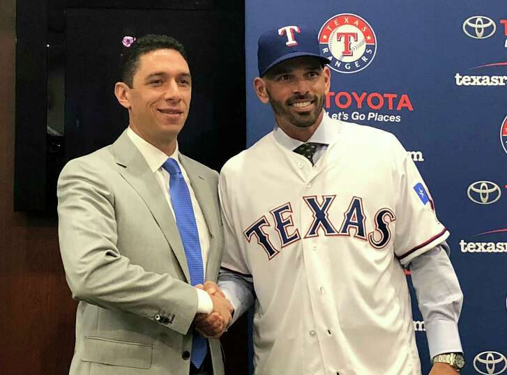Texas Rangers' general manager Jon Daniels shakes hands with new manager Chris Woodward during a press conference Monday, Nov. 5, 2018, in Arlington, Texas. The Rangers formally introduced Woodward, the Dodgers third base coach, as their new manager Monday, just more than a week after Los Angeles lost in the World Series for the second year in a row. Texas had been the last team to do that, in 2010 and 2011.  (AP Photo/Stephen Hawkins)