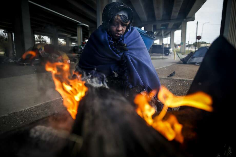 Tony Sampson, who received a blanket from Star of Hope's Love in Action van, tries to warm up by a fire under the Eastex Freeway as temperatures hover in the 30s Tuesday, Jan. 2, 2018 in Houston. Photo: Michael Ciaglo/Staff Photographer