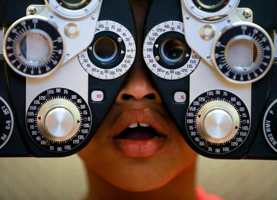 Chaise Perry, 8, looks through a phoropter to get his new prescription during an event to get eye glasses to low-income students from the Houston area, Wednesday, Jan. 10, 2018, in Cypress. Photo: Jon Shapley/Staff Photographer