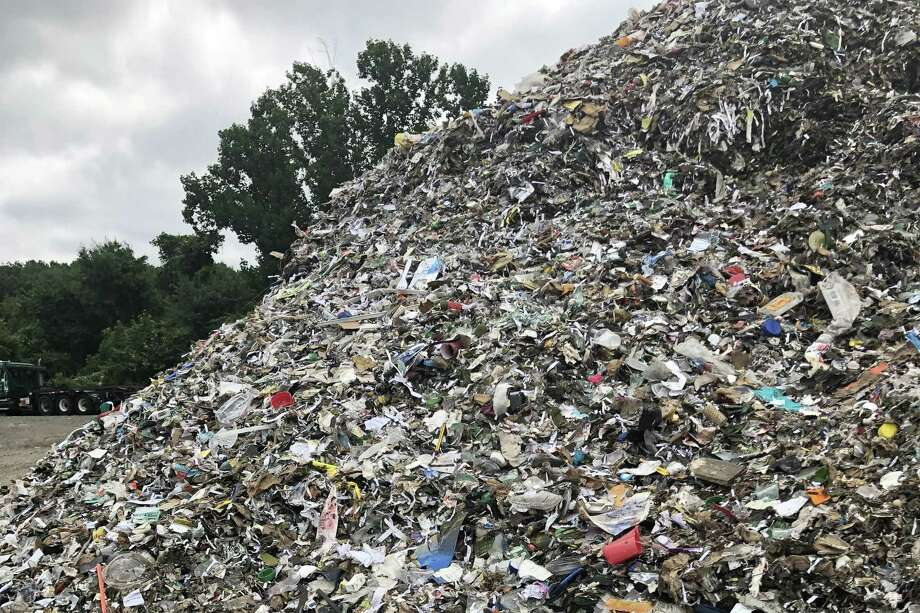 A pile of recycled glass outside of a local processing facility. The glass is contaminated from small and nonrecyclable items in the single stream. It also becomes a contaminent for other recycled materials when it breaks. Photo: Contributed Photo / Contributed Photo / The News-Times Contributed