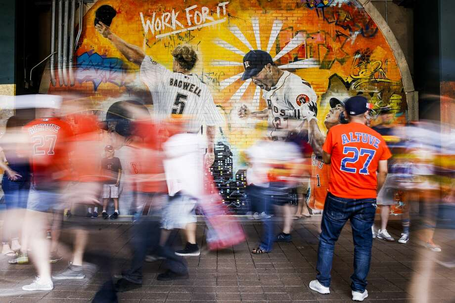 Fans walk past the Astros Street Art display in Home Run Alley as they head to their seats before the Houston Astros home opener against the Baltimore Orioles at Minute Maid Park Monday, April 2, 2018 in Houston. The graffiti artwork was painted by local artist Franky Cardona. Photo: Michael Ciaglo/Staff Photographer