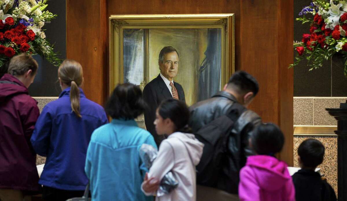 People crowd around to sign the guestbook after the doors to the George Bush Presidential Library open on Friday, Dec. 7, 2018. Former President George H.W. Bush was buried at a gravesite on the library's grounds on Thursday. The gravesite is expected to be opened to the public on Saturday, but heavy rains in the area may cause a delay in public access to the site.