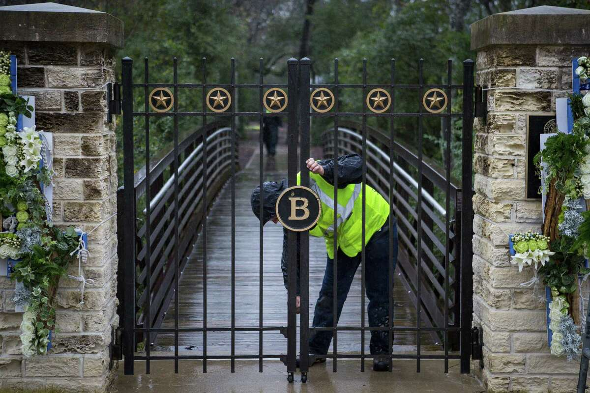 A member of the grounds crew at the George Bush Presidential Library closes the gate to the gravesite while work is done, Friday, Dec. 7, 2018. Former President George H.W. Bush was buried at a gravesite on the library's grounds on Thursday. The gravesite is expected to be opened to the public on Saturday, but heavy rains in the area may cause a delay in public access to the site.