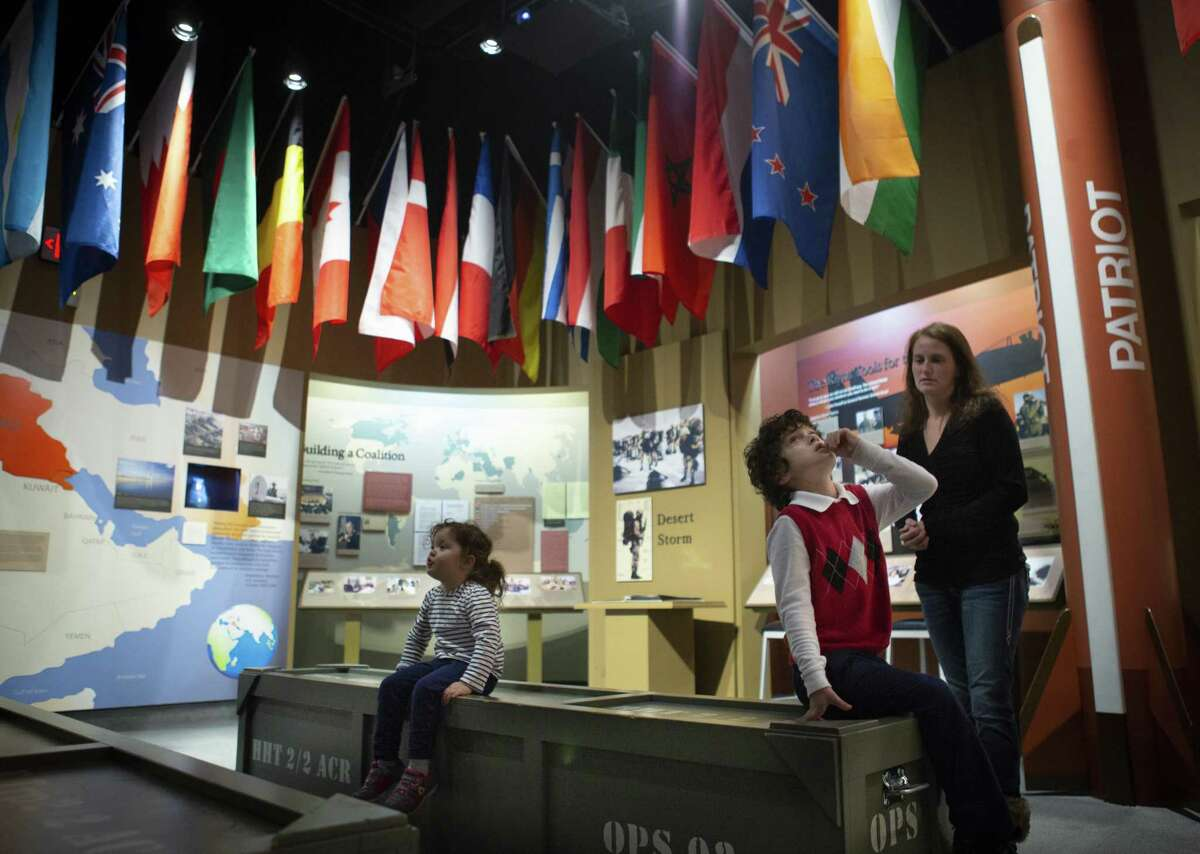 Sharlene Dickey and her two children, Elijah, 7, and Isabella, 3, looks a display about the Gulf War at the George Bush Presidential Library, Friday, Dec. 7, 2018. Former President George H.W. Bush was buried at a gravesite on the library's grounds on Thursday. The gravesite is expected to be opened to the public on Saturday, but heavy rains in the area may cause a delay in public access to the site.