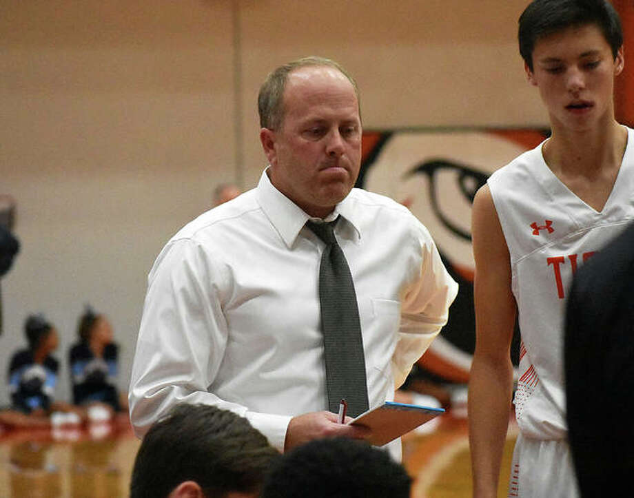 Edwardsville assistant boys' basketball coach Chris Jones listens to head coach Dustin Battas during a timeout in Tuesday's game against Belleville East at Lucco-Jackson Gymnasium. Jones, a former Division I assistant coach, is in his first season on the EHS coaching staff. Photo: Matt Kamp/Intelligencer