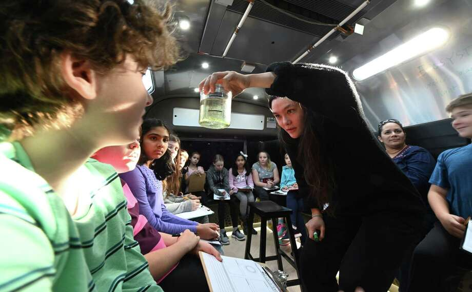 Scientist and instructor Li Murphy shows students from the Woodland Hill Montessori School an example of an ecosystem during a demonstration on the Bio Bus which made a stop at their school Friday Dec. 7, 2018 in North Greenbush, N.Y.  (Skip Dickstein/Times Union) Photo: SKIP DICKSTEIN, Albany Times Union / 20045633A
