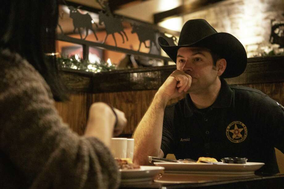 Montgomery County Constable's Office Precinct 4 Detective Cory Arnold listens to his girlfriend Bianca Bickford as they eat their breakfast during the Montgomery County Constable's 5th annual fundraising breakfast for Childrens Safe Harbor on Friday, Dec. 7, 2018 at LongHorn Steakhouse in Spring. Proceeds from the fundraiser goes toward investigation and treatment assistance for children who are victims of physical and sexual assault. Photo: Cody Bahn, Houston Chronicle / Staff Photographer / © 2018 Houston Chronicle