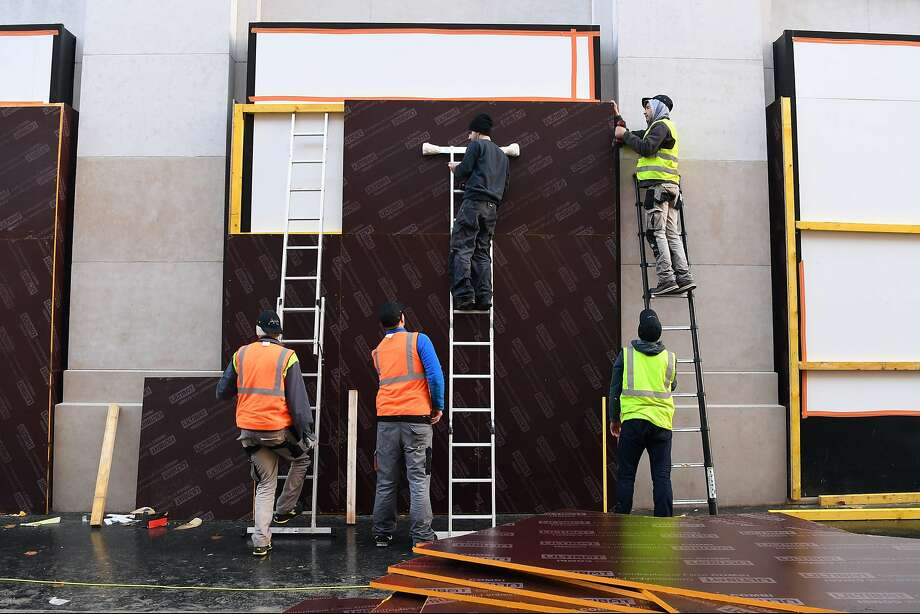 Workers place a board to protect a store window in the plush Champs-Elysees neighborhood in Paris. Photo: Alain Jocard / AFP / Getty Images