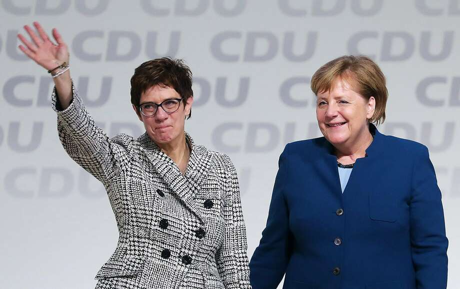 Annegret Kramp-Karrenbauer (left) waves to party members while standing next to Chancellor Angela Merkel. She is the favorite to succeed Merkel. Photo: Krisztian Bocsi / Bloomberg