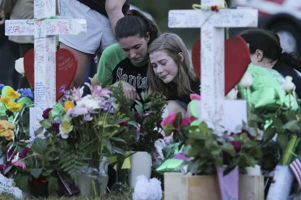 People gather in front of Santa Fe High School to share the grief and show give their respects on Monday, May 21, 2018 in Santa Fe. The town is still trying to cope with the pain of the high school shooting that happened on Friday, May 18, 2018.