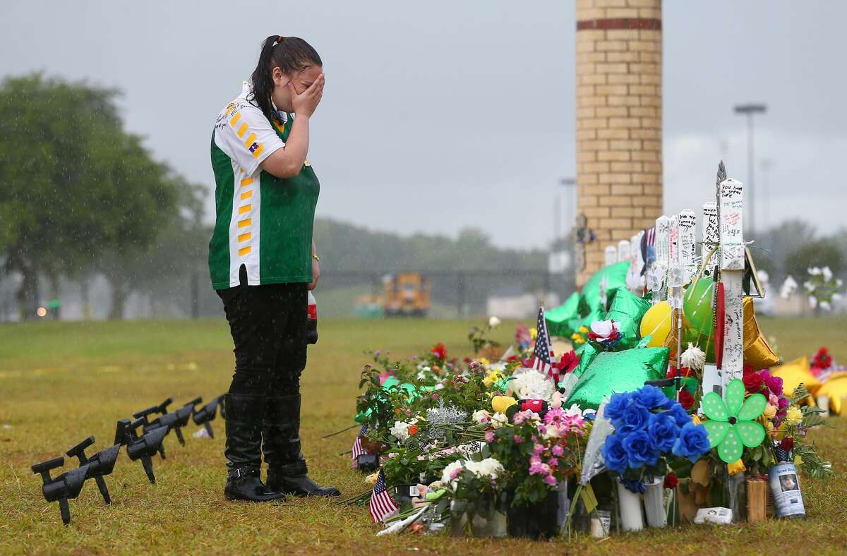 Sierra Dean, 16, grieves while visiting the memorial for Kimberly Vaughan, her best friend, in front of the Santa Fe High School. Vaughan, seven other students, and two staff members were killed by a gunman last year.
