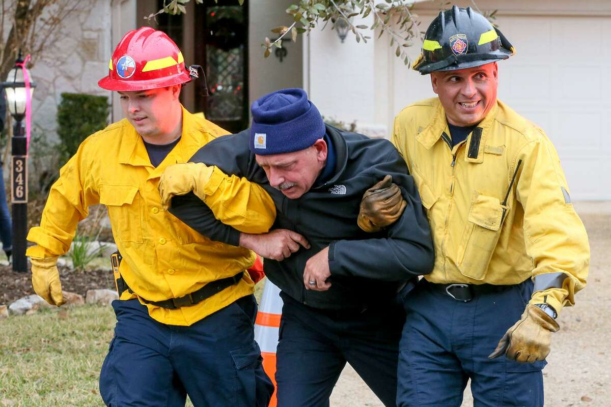 Firefighters rescue a resident, played by an instructor, on Thursday, Dec. 6, 2018 during a wildfire training exercise in the Roseheart neighborhood on the North Side.