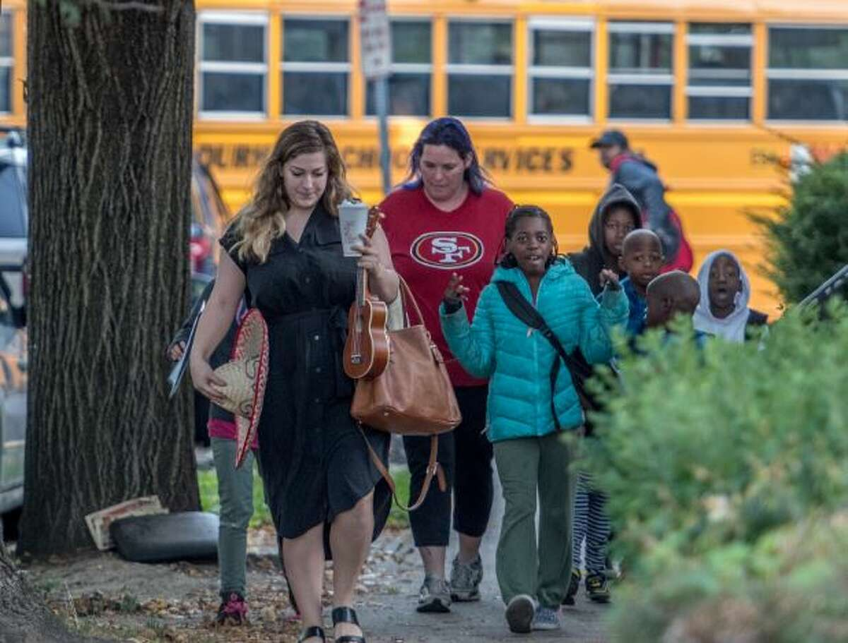 Students on their way to Pine Hills Elementary School on National Walk to School Day as a school bus passes behind them on Wednesday Oct. 4, 2017 in Albany, N.Y.