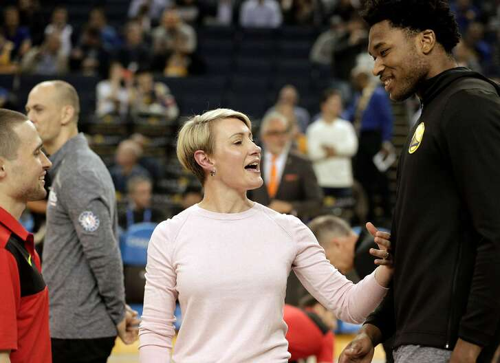 Warriors center Damian Jones, right, talks with Chelsea Lane and John Dusel, both former members of the Warriors training staff now with the Hawks during warmups before the Golden State Warriors played the Atlanta Hawks at Oracle Arena in Oakland, Calif., on Tuesday, November 13, 2018.