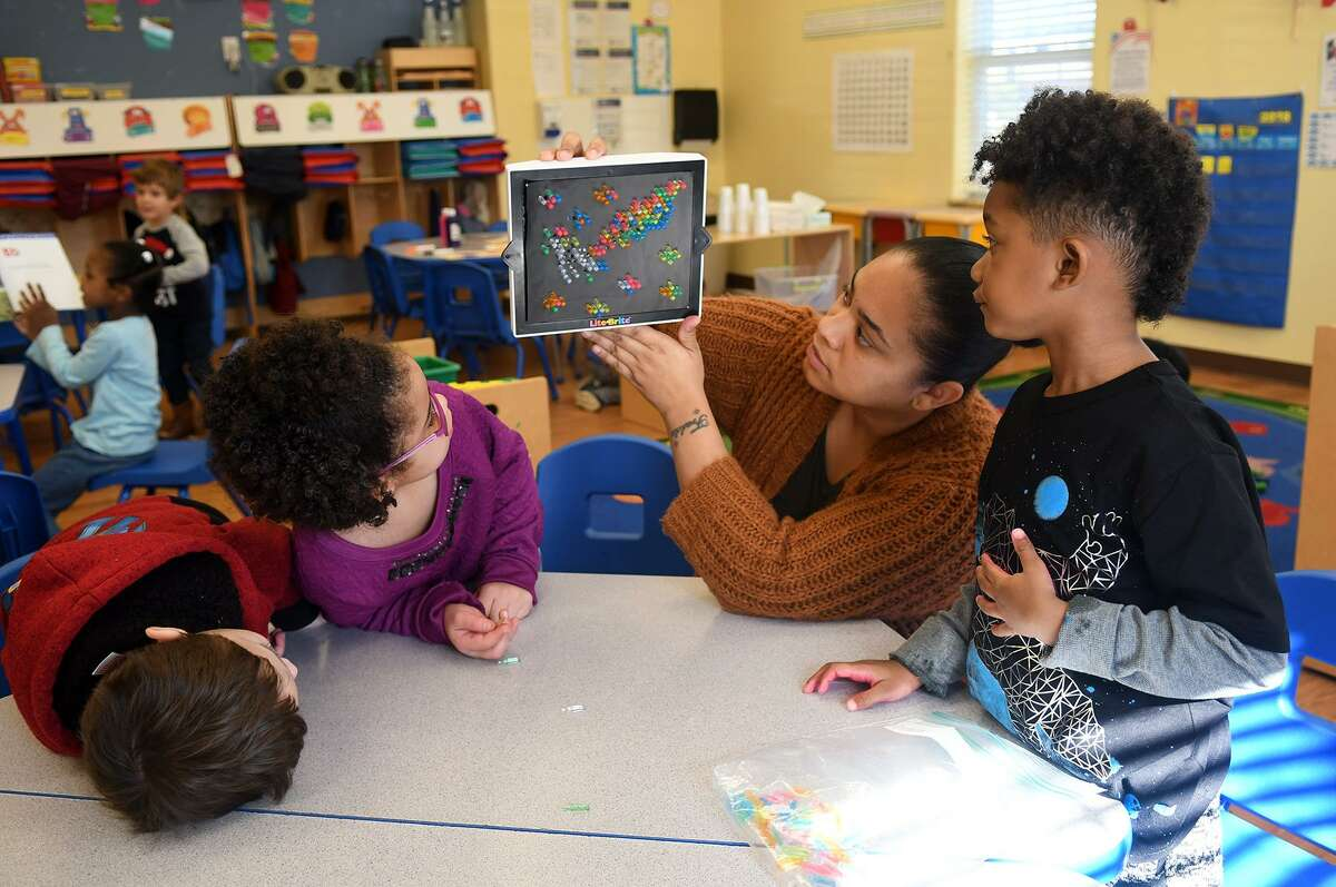 Shelly Thomas, center, a pre-k teacher at the Goddard School in Cypress, helps junior kindergartners Kyle Pointon, 4, from left, Piper Evans, 5, and Evan Edwards, 5, try out a Lite Brite game during a toy test in their Big Thinkers class on Dec. 5, 2018.