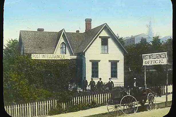This photo of the Seattle Post-Intelligencer's first building was taken on Mill Street around 1881. Mill Street is now called Yesler Way. The tower of Providence Hospital can be seen in the background.
