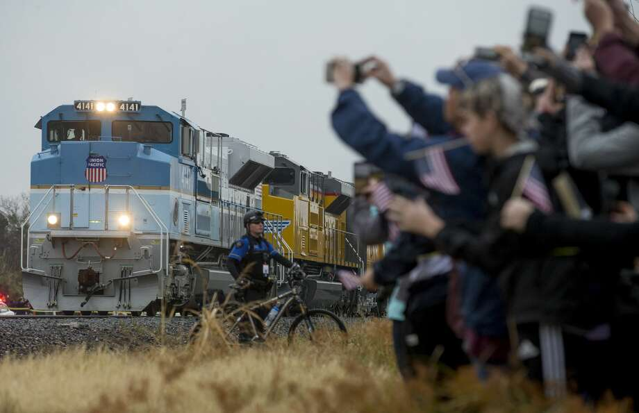 People record and watch the arrival of the train carrying former President George H.W. Bush's body Thursday, Dec. 6, 2018, in College Station, Texas. Photo: Godofredo A. Vasquez/Staff Photographer