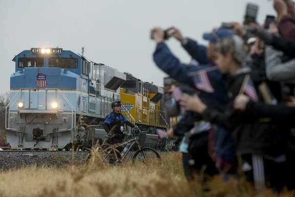 People record and watch the arrival of the train carrying former President George H.W. Bush's body Thursday, Dec. 6, 2018, in College Station, Texas.