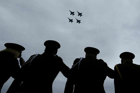 "Texas A&M University Corps of Cadets salute as the Unites States Navy perform a 21-strike aircraft ""missing man"" formation to honor former President George H.W. Bush during his arrival and internment at the George Bush Presidential Library and Museum, Thursday, Dec. 6, 2018, in College Station."