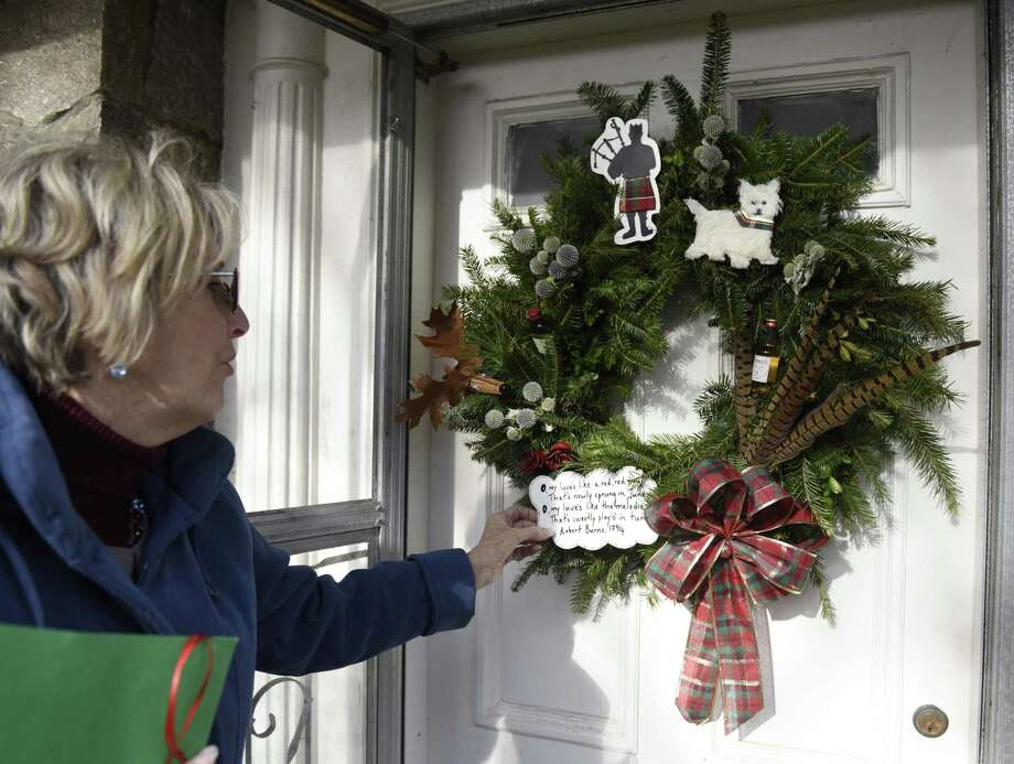 Design Chair Georgia Nostrand points out Amanda Cook's first-place wreath in the International/Cultural category at Shippan Point Garden Club's 39th annual Doors of Shippan wreath competition in the Shippan neighborhood of Stamford, Conn. Thursday, Dec. 6, 2018. Nearly 50 homes decorated wreaths for the competition in a variety of categories including traditional, all-natural, religious, creative/unconventional and more. Photo: Tyler Sizemore / Hearst Connecticut Media / Greenwich Time