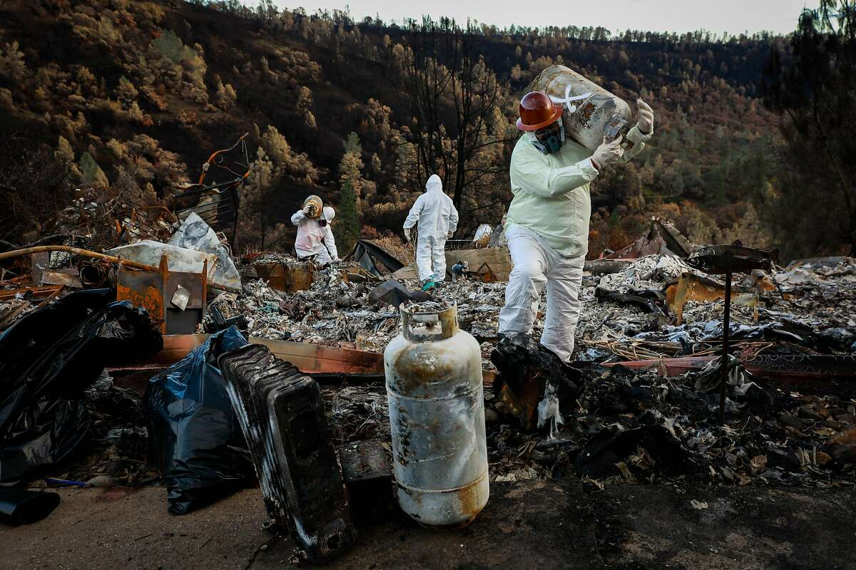 EPA contractors carry propane tanks through a property that was destroyed by the Camp Fire while looking for hazardous materials in Paradise, California, on Wednesday, Dec. 5, 2018.