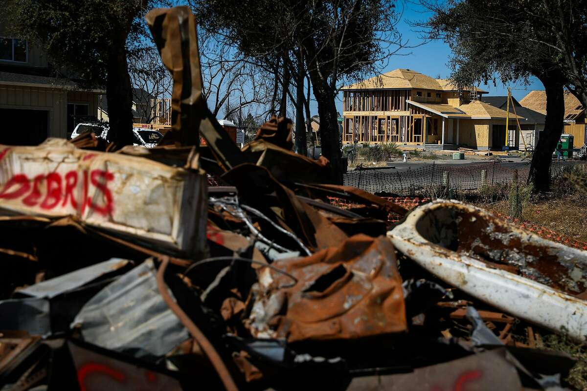 A house is seen under construction while debris from the Tubbs fire is seen (left) in the Coffey Park neighborhood nearly one year after the Tubbs fire ravaged the area in Santa Rosa, California, on Thursday, Sept. 20, 2018.