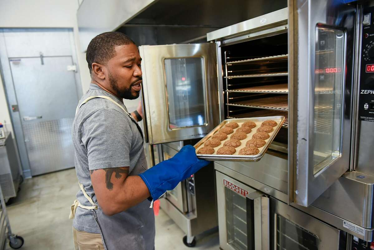 Owner Anthony Lucas pulls a batch of cinnamon spice cookies out of an oven at Anthony's Cookies shop and bakery in Berkeley, CA, on Friday November 2, 2018.