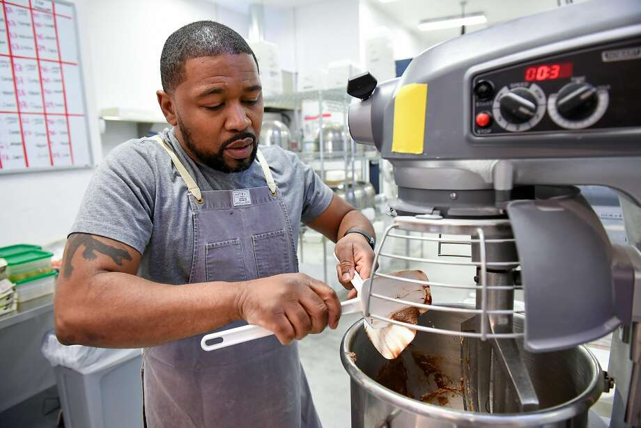 Anthony Lucas scrapes cookie batter into a mixer while working in the kitchen at Anthony's Cookies shop and bakery. Photo: Photos By Michael Short / Special To The Chronicle