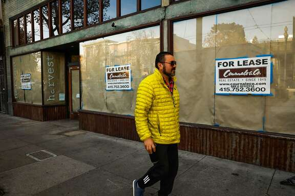 A person passes by a shuttered storefront on Market Street in the Castro, a neighborhood in San Francisco that's been hit hard by retail vacancies, on Monday, Oct. 29, 2018.