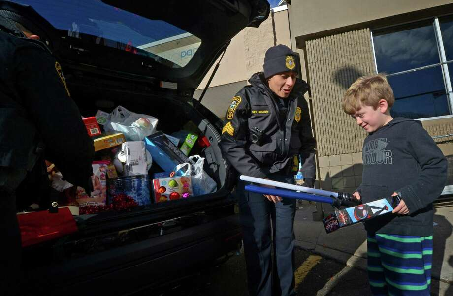 "Norwalk police seargent Sofia Gulino receives a donation from Norwalk resident P.J. Small, 6, during the Norwalk Police Department third annual Stuff-A-Cruiser"" toy drive event Friday, December 7, 2018, at the Walmart on Main Ave. in Norwalk, Conn. Officers accepted donations of new, unwrapped toys for children ages infant-15 years old which benefit local families in need through the Domestic Violence Crisis Center, the Human Services Council, The Open Door Shelter and the Norwalk Housing Authority. Photo: Erik Trautmann / Hearst Connecticut Media / Norwalk Hour"
